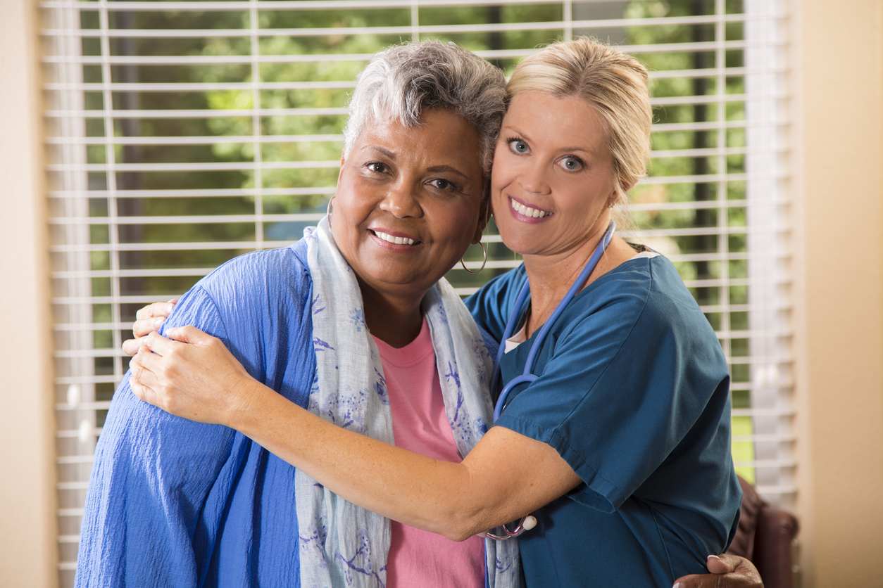 Close-up view of a caring home healthcare nurse with her senior adult female patient at home or an assisted living facility.  The female patient gets an affectionate hug from her nurse.  Backyard can be seen through the windows.